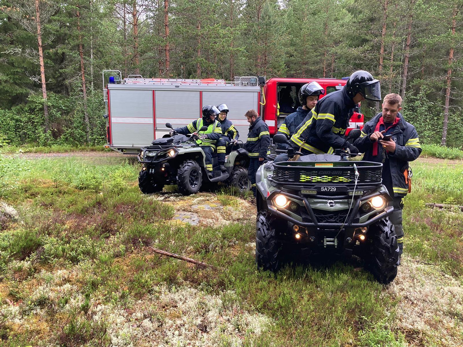VPK:n harjoituksissa. Kaksi mönkijää miehistöineen paloauton edustalla maastossa.