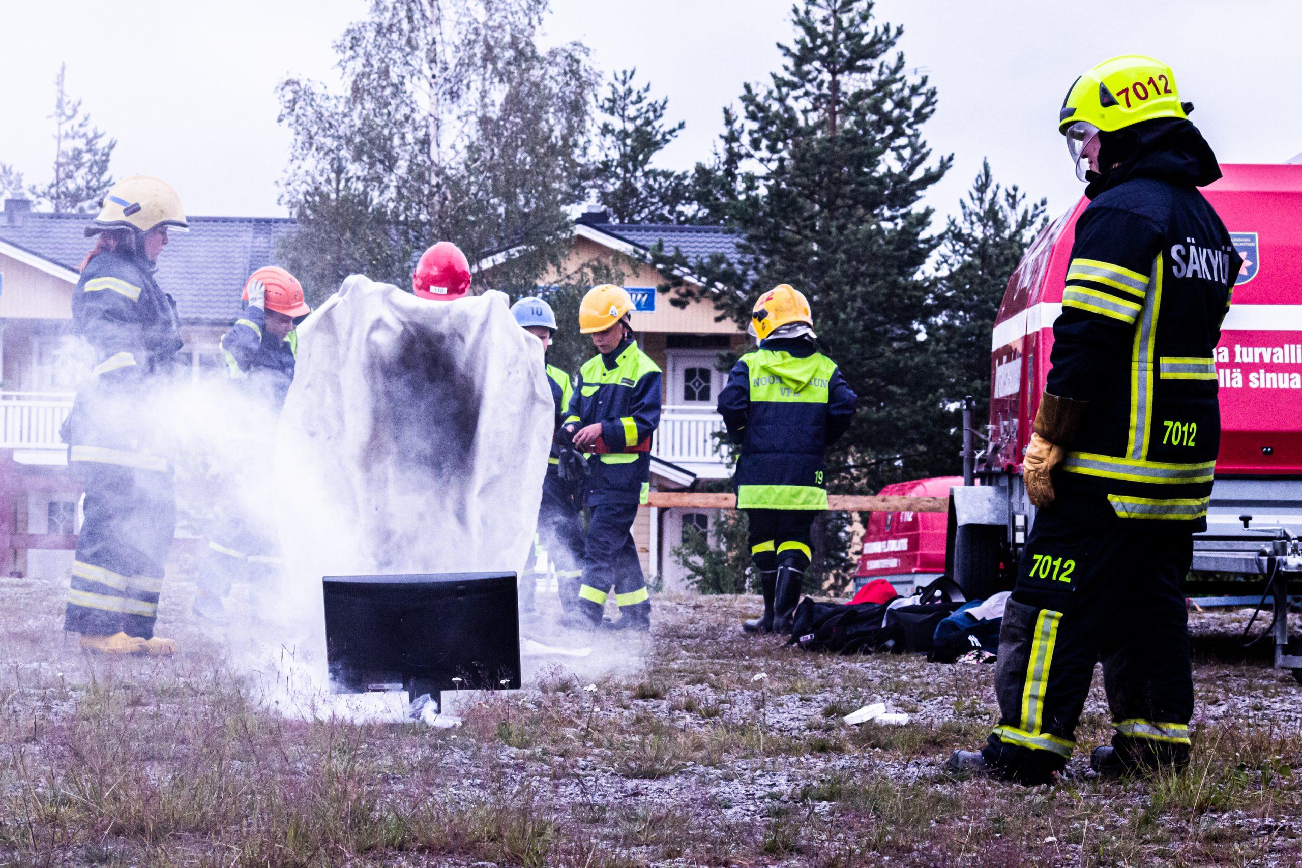 Palokuntanuoret harjoittelevat näytön alkusammutusta ulkona, aikuinen seuraa vieressä. (Kuva: LSPeL)