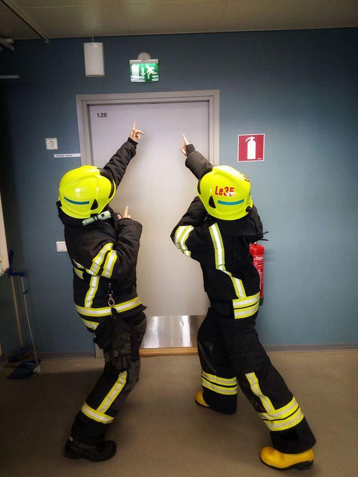 Kaksi palokuntanuorta osoittavat exit-merkkiä rakennuksen sisällä. (Kuva: LSPeL)