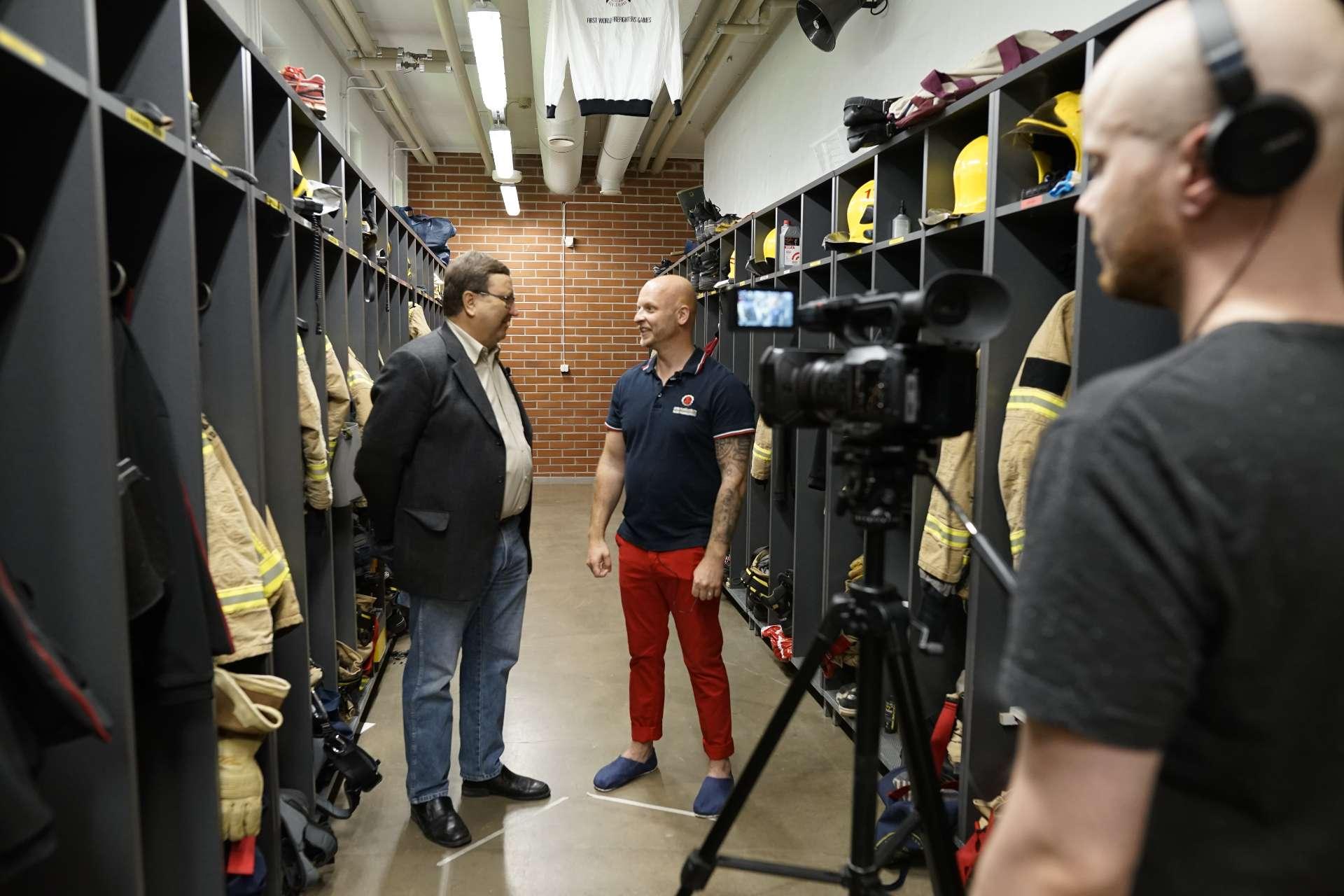 MentalFireFit-hankkeen kuvaukset: palomiestä haastatellaan paloaseman pukuhuoneessa.