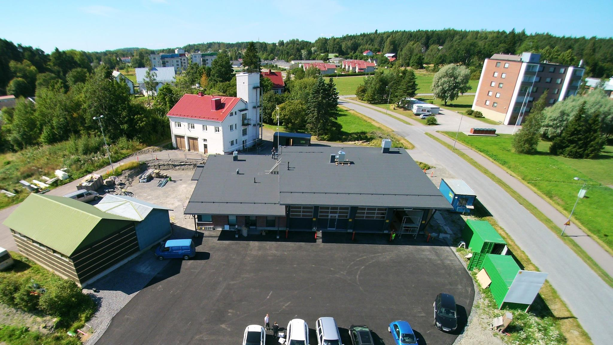 """Kuva: Paloasemaa rakennetaan. Taustalla vaalea rakennus on vanha paloasema ja vasemmalla vihreä on kalustohalli sekä harmaa osa """"sosiaalitiloja"""". Kuva: Piikkiön VPK ry."""